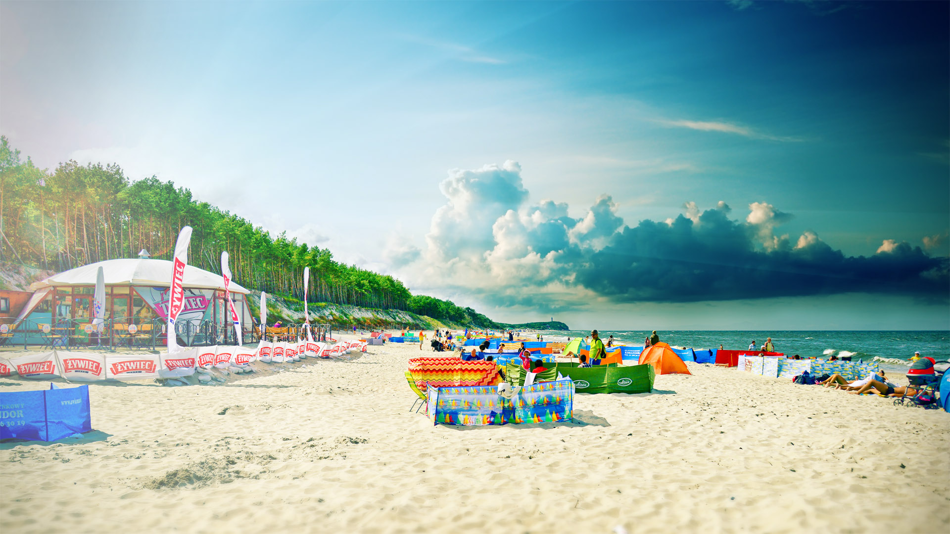 Słoneczny dzień, za parawanami opalają się turyści. Przy wydmie bar plażowy.